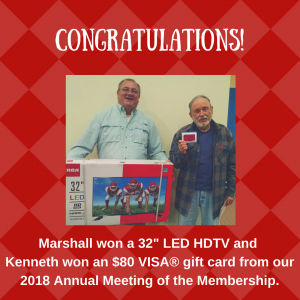 "2018 Annual Meeting Door Prize winners: Marshall holding a 32"" LED HDTV he won, and Kenneth holding an $80 VISA gift card he won."