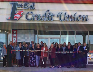 Hanover branch staff and community members gather for ribbon cutting of a ribbon with actual money